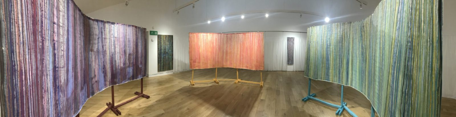 Panoramic photograph of the interior of Serenade, the central piece within Ruth Dent's installation, Breathing Space. The three central canvases: Blue and Red, Red and Yellow and Yellow and Blue can be seen. These represent three steps around the colour wheel. A contemporary abstract art installation.