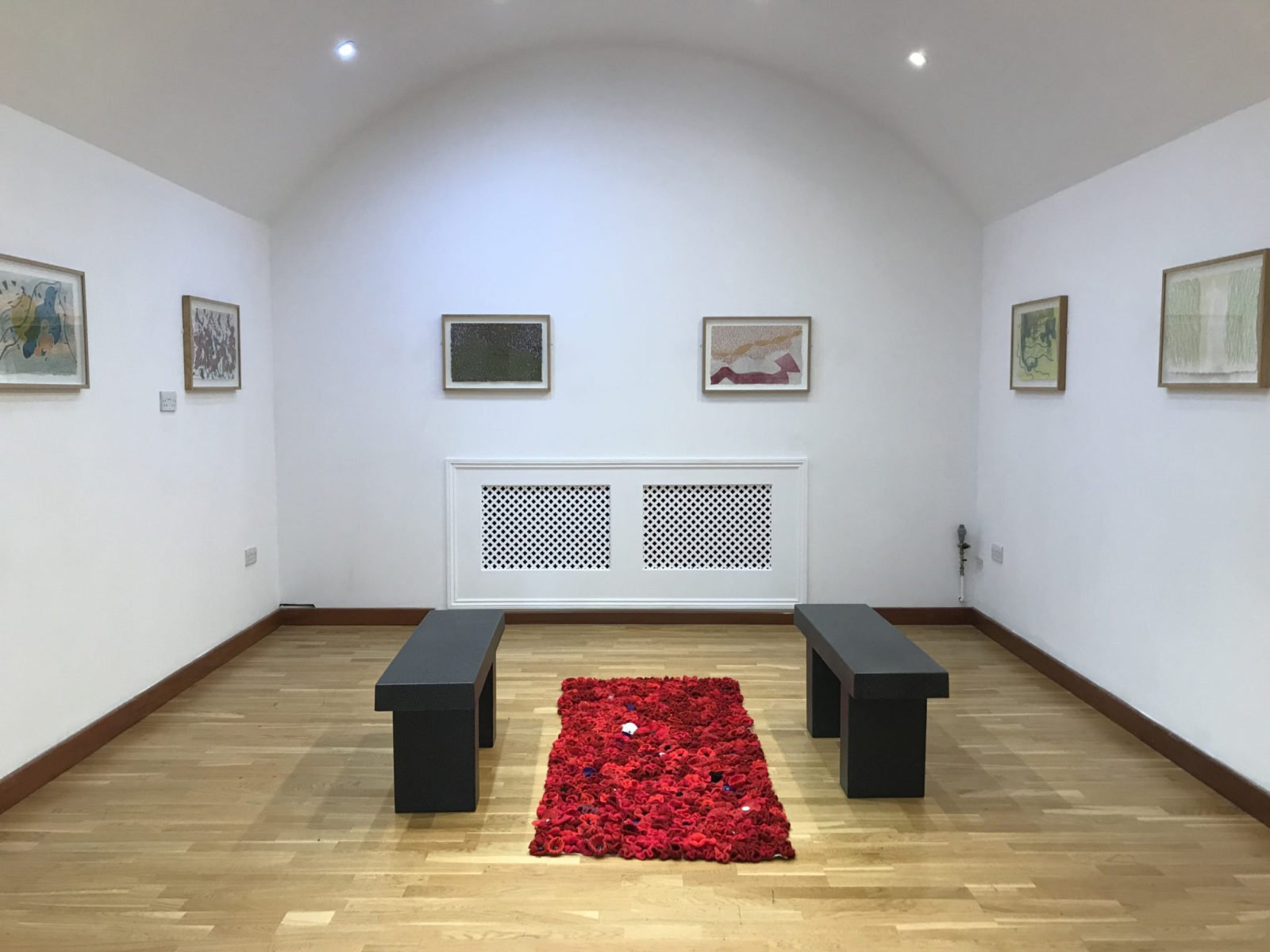 Ruth Dent's Britten War Requiem Prints exhibited at the Royal Engineers Museum, with a carpet of poppies